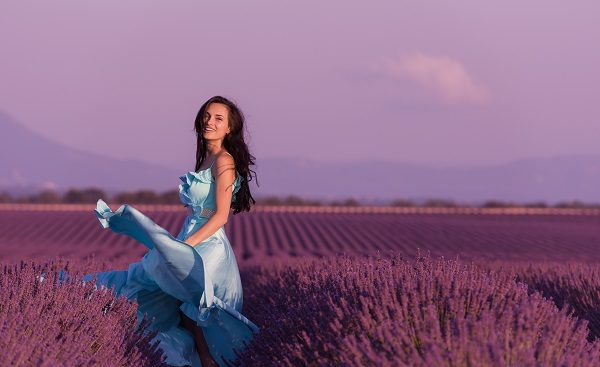 Russian woman running in lavender flower field wearing a nice dress