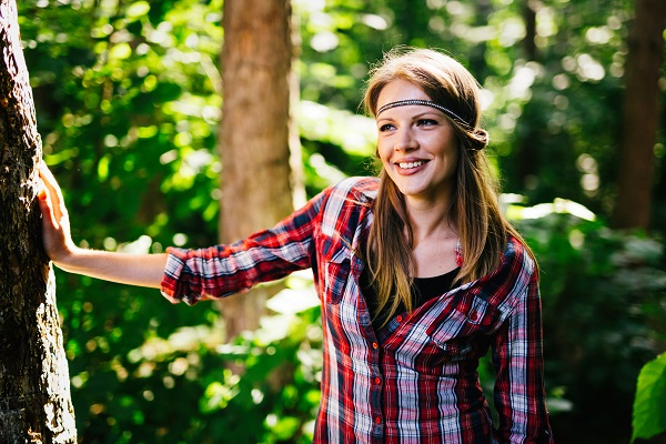Beautiful smiling Russian woman surrounded by green leaves in the forest