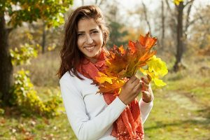 Young Russian girl with autumn leaves in her hand on a sunny day