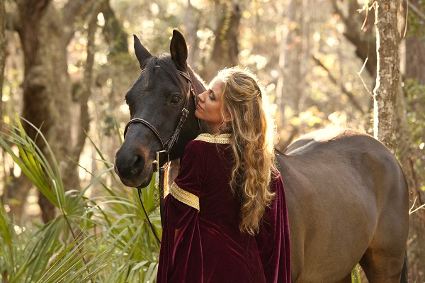Blonde-haired Russian woman in a medieval dress with a horse in the forest
