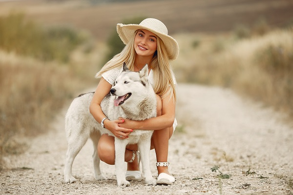 Elegant and stylish Russian girl posing with a dog for the camera in an autumn field