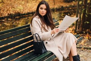 Beautiful stylish Russian brunette girl with a newspaper resting on a bench in an autumn park