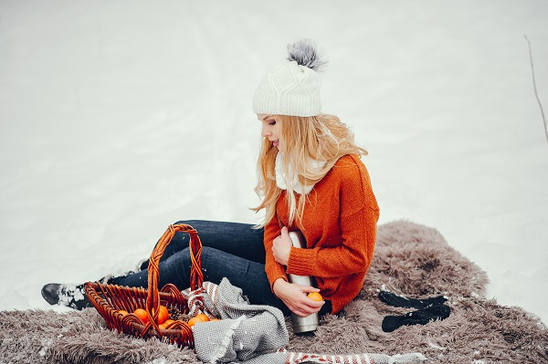 Beautiful young Russian girl in a cute orange sweater looking sideways posing for the camera
